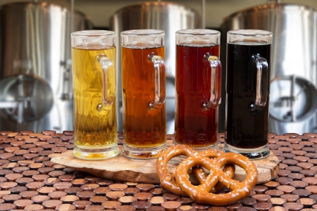 beer flight of four sampling mugs of light and dark craft beer with beer fermenter background