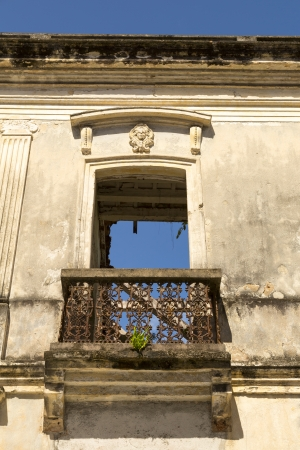 colonial balcony door in the ruins with blue sky showing through