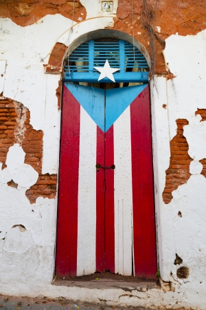 obsolete wooden door with Puerto Rican flag painted on it photo