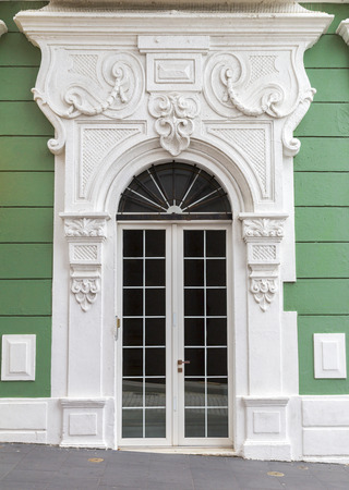 renovated: Renovated charming old Spanish door with decorative portal over green wall in San Juan, Puerto Rico