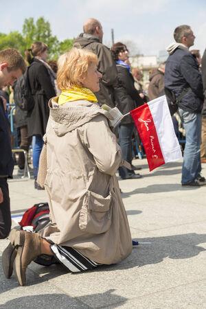 bandera de polonia: VARSOVIA, Polonia - 27 de abril: De rodillas mujer con una bandera de Polonia durante la transmisi�n p�blica de la misa de canonizaci�n del Papa Juan Pablo II en la Plaza de Pilsudzki en Varsovia el 27 de abril de 2014.