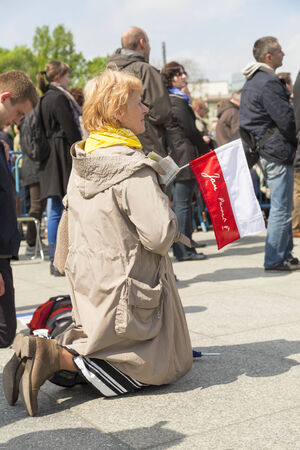 polish flag: WARSAW, POLAND - APRIL 27: Kneeling woman with a Polish flag during public transmission of canonization mass of Pope John Paul II at the Pilsudzki Square in Warsaw on April 27, 2014.