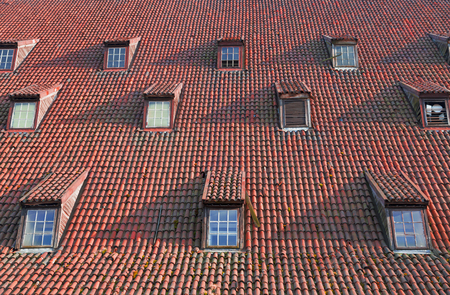 casement: Vintage pitched red tile roof with tiny garret casement widows Stock Photo