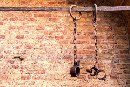 hand chain: Middle aged prisoners chains and cuffs over a brick wall Stock Photo