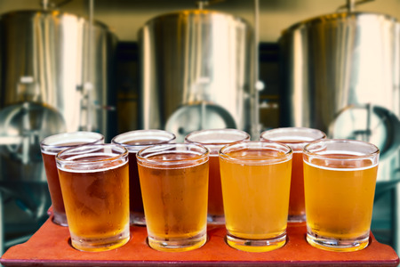 pilsner glass: Beer flight of eight glasses of craft beer on a serving board with fermenting tanks background.