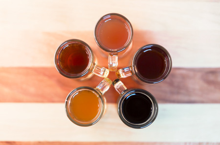 Beer flight of five sampling mugs of light and dark craft beer. Circle of little mugs, top view with handles to the center, flower shape.