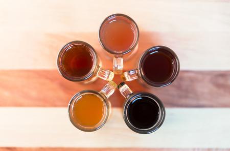 Vol de bière de cinq tasses échantillonnage de bière artisanale lumière et l'obscurité. Cercle de petites tasses, vue de dessus avec des poignées au centre, en forme de fleur. Banque d'images - 31475944
