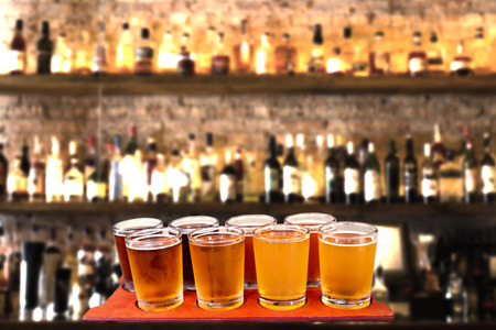 tavern: Beer flight of eight sampling glasses of craft beer on a bar countertop.