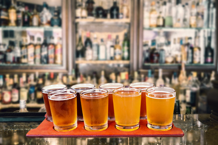 バーの料理板クラフト ビールのサンプリングのコップ 8 杯のビール飛行。
