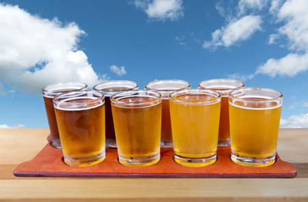 Beer flight of eight sampling glasses of craft beer on a serving board with blue cloudy sky background.