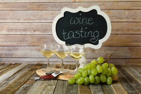 White wine flight with chalkboard sign and grapes