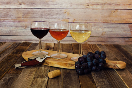 Wine flight on cutting board with grapes, cork and bottle opener
