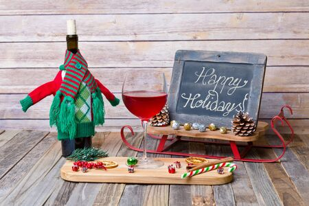 Holiday glass of red wine with chalkboard sign and decoration