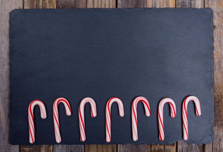 top seven: Holiday striped candy canes on dark board and wooden background. Top view, flat lay. Stock Photo