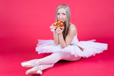 Pretty blond ballerina is happy to eat a pizza slice.