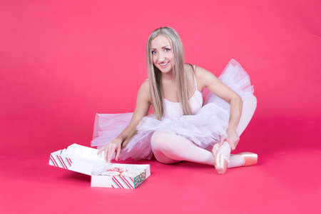 Pretty blonde ballerina in tutu skirt reaching for a donut on pink backdrop.