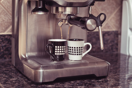 Home espresso machine on kitchen countertop making two cups coffee.