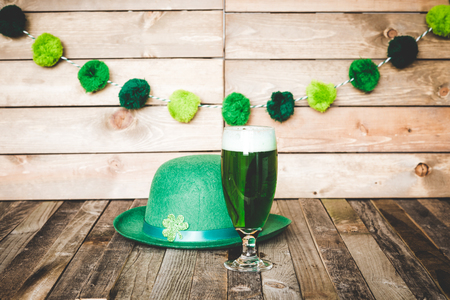 Glass of green beer with Irish festive hat on wooden background. Tabletop, side view. Archivio Fotografico
