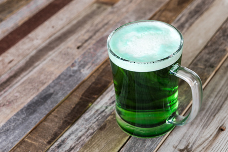 Single mug of green beer on wooden background. Tabletop, side view.