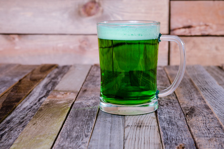 Single mug of green beer on wooden background. Tabletop, front view. Stock Photo