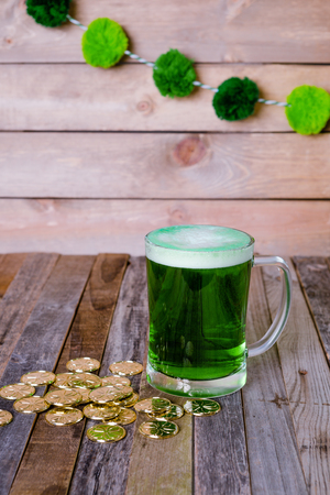 St. Patrick's mug of green beer with golden coins on wooden background. Tabletop, front view.