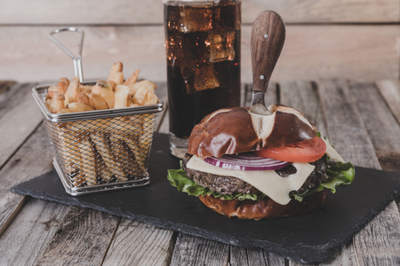 Gourmet cheeseburger with French fries and drink on wooden background