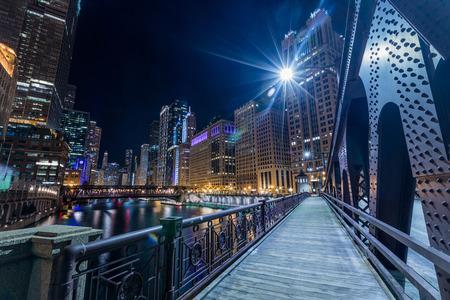 シカゴのダウンタウンは、橋から夜に川のそばの景色を照らしました