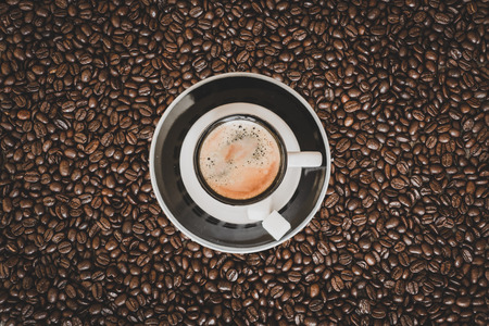 Single small espresso coffee cup on roasted coffee beans background