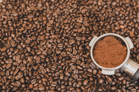 Metal espresso machine scoop with ground coffee on roasted coffee beans background