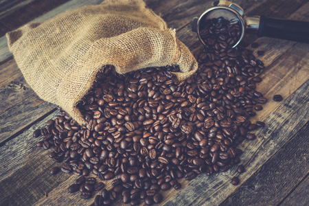 Roasted coffee beans in a burlap bag on wooden table background with espresso machine scoop