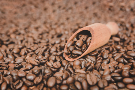 Wooden scoop full of coffee beans on roasted coffe beans background
