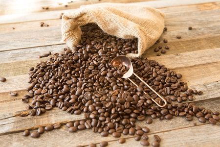 Roasted coffee beans in a burlap bag on wooden table background with copper scoop