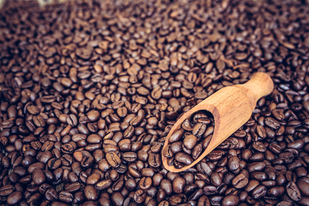 Wooden scoop full of coffee beans on roasted coffee beans background