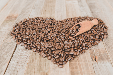 Roasted coffee beans in a shape of heart on wooden background