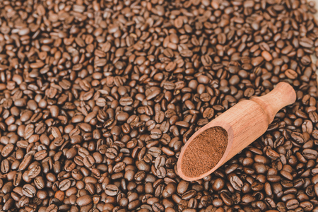 Wooden scoop with ground coffee on roasted coffee beans background