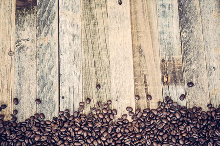 Roasted coffee beans spread on bottom part of wooden table background