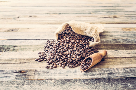 Roasted coffee beans in a burlap bag on wooden table background 版權商用圖片