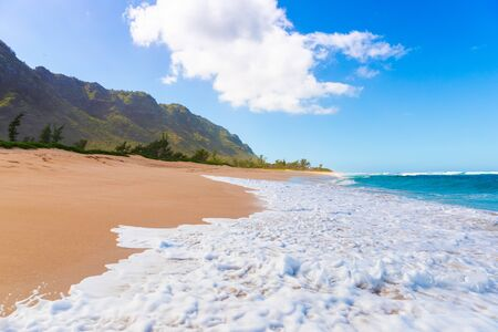 Turquoise ocean wave on tropical sandy beach with mountains in background 版權商用圖片