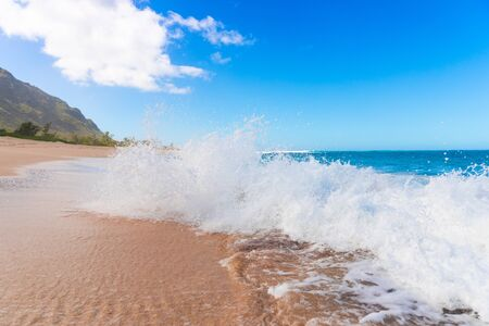 Turquoise ocean wave splash on tropical sandy beach with mountains in background 版權商用圖片