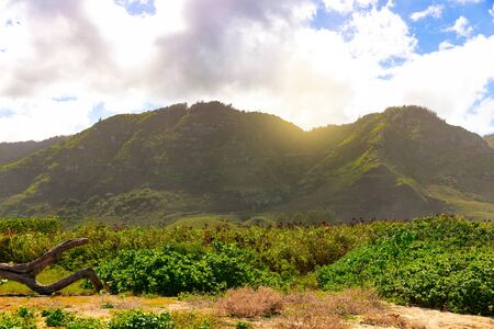 Hawaiian mountains by the ocean coastline with cloudy sky