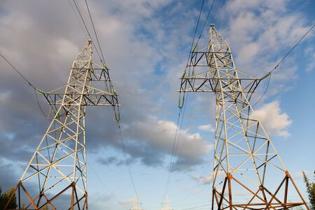 volts: Two high-voltage towers on a background of the cloudy sky Stock Photo