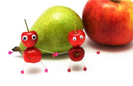 Two amusing little men from a sweet cherry on a background of a pear and an apple photo