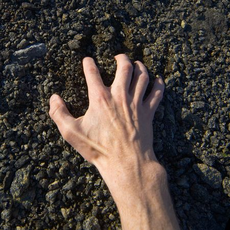 stony: Mans hand clinging stony ground