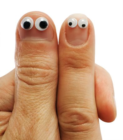 Two fingers of hands with doll eyes Stock Photo
