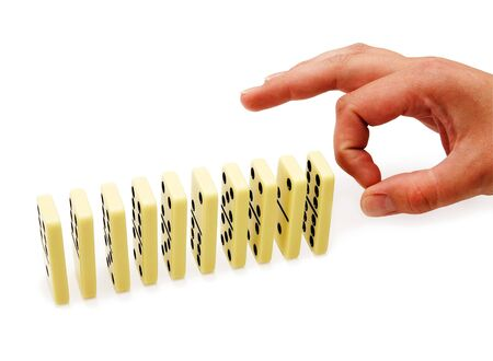 regimented: Fingers in click are going to drop a dominoe Stock Photo