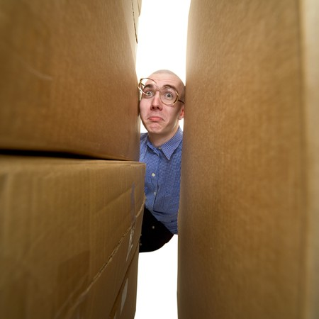stockman: Male face between pile cardboard boxes on white
