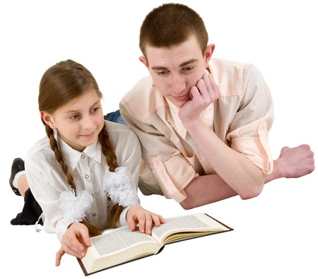 Girl and young man reading book in a reclining position on white photo
