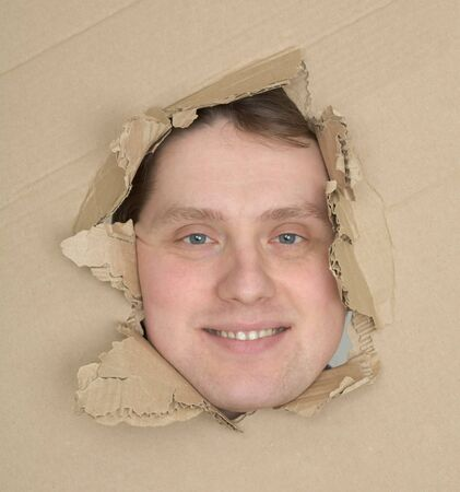 Male face look up through hole cardboard box photo