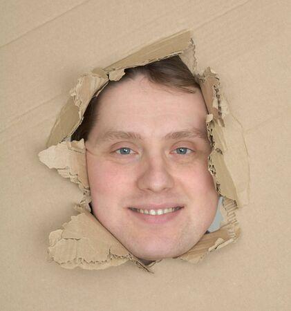 Male face look up through hole cardboard box photo