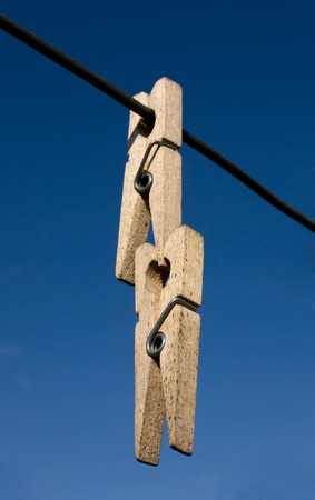 clothespeg: Two wooden clothes-peg hang a rope on sky background